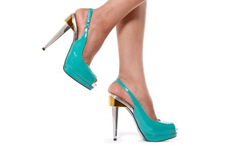 Closeup shot of young womans legs in fashionable high heel turquoise shoes, on white