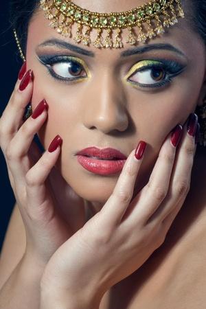 Beautiful asianindian woman with bridal makeup and jewelry, closeup shot photo