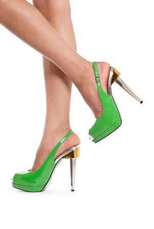 Spring fashion: closeup shot of young womans legs in fashionable high heel green shoes, on white Stock Photo