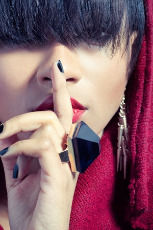 Closeup picture of young woman with finger on red lips, signalling to keep secret photo