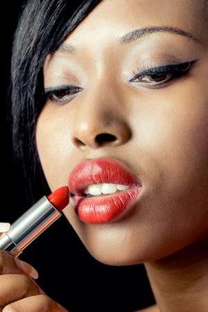 Beautiful woman applying red lipstick, closeup shot