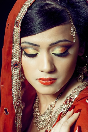 Beauty portrait of a young indian woman in traditional clothing with bridal makeup and jewelry, closeup shot photo