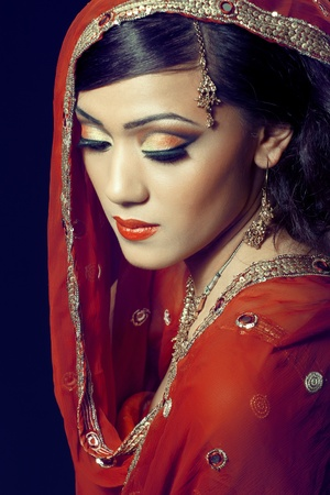 Beauty portrait of a young indian woman in traditional clothes with bridal makeup and jewelry, closeup shot photo