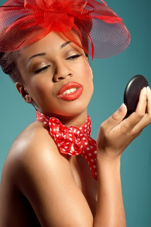 Beautiful smiling pinup girl holding a mirror and checking makeup Stock Photo - 9992206