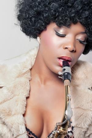Young beautiful african woman playing a saxophone, closeup shot Stock Photo