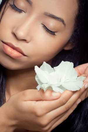 Beautiful young woman holding a white flower near her face, spabeach relaxation concept photo