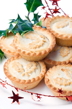 british foods: Traditional christmas mince pies on table decorated with tinsel and holy Stock Photo