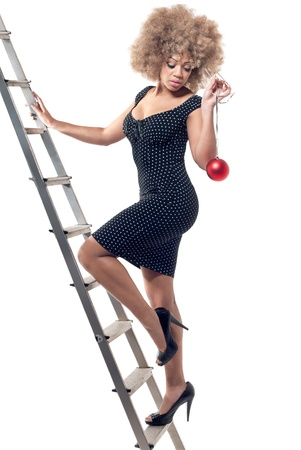 tiredness: Young beautiful woman climbing an infinite ladder holding a Christmas ball, full body portrait. Long-term Christmas preparations, fuss and pre-holiday tiredness concept. Stock Photo