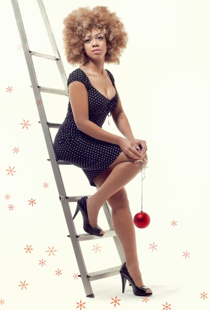 tiredness: Young beautiful woman sitting on a ladder holding a Christmas ball, full body portrait. Long-term Christmas preparations, fuss and pre-holiday tiredness concept