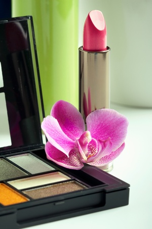 Natural cosmetics concept: lipstick and eyeshadow palette with orchid flower, closeup shot photo
