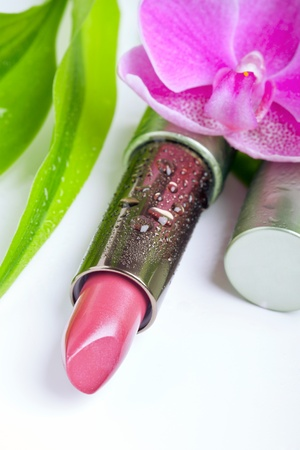 Natural cosmetics concept: lipstick with bamboo leaves and an orchid flower, isolated on white photo