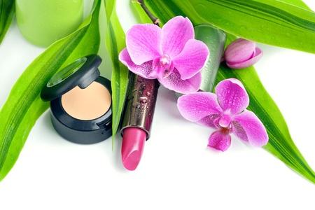 concealer: Concetto di cosmesi naturale: correttore e un rossetto con le foglie di bamb� e un fiore di orchidea, isolato su bianco