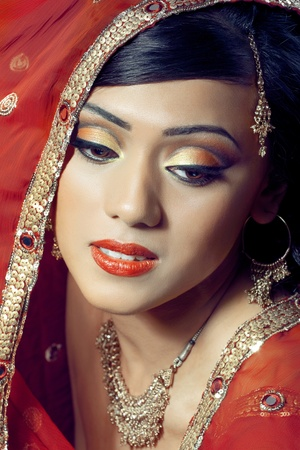 Portrait of young beautiful happy indian bride with bright makeup and golden jewelry