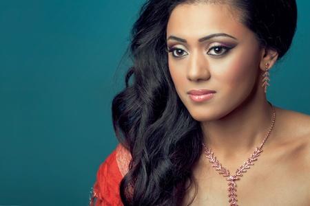 블루에 고립 된 긴 머리를 가진 아름 다운 젊은 아시아  인도 모델의 초상화
