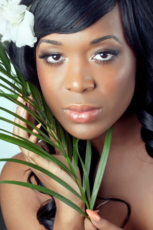 Beautiful young woman with a tropical flower in her hair and palm leaves, close-up shot  photo