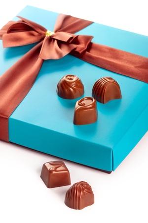 Milk chocolates and beautiful gift box with ribbon bow, closeup shot
