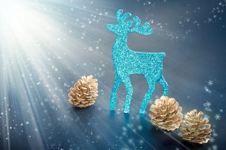 Christmas decorations: reindeer figure and golden cones with snowflakes in light rays background, closeup shot  photo