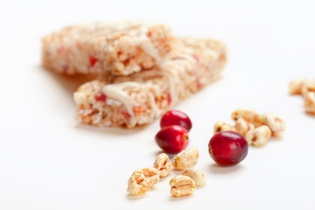 Cereal bars with puffed wheat and cranberries, closeup shot, focus on wheat flakes photo