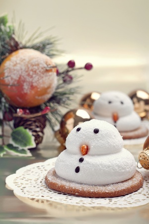 Two marshmallow snowmen biscuits with Christmas decorations, closeup shot photo