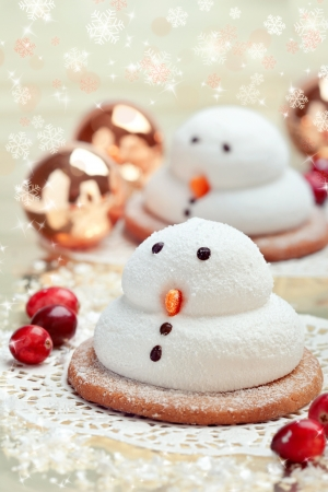 Two traditional marshmallow snowmen biscuits with Christmas decorations, closeup shot