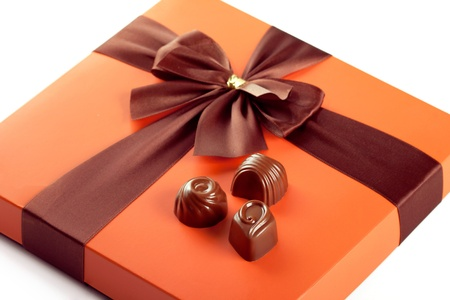 Chocolate sweets and beautiful gift box with ribbon bow, closeup shot