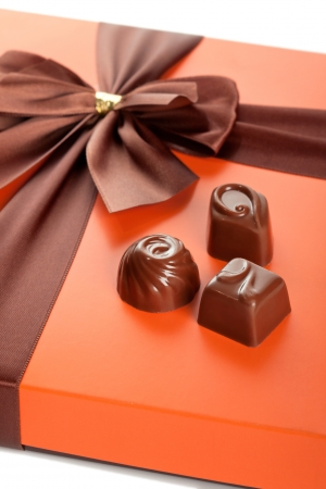 Chocolate sweets and beautiful gift box with ribbon bow, closeup shot photo