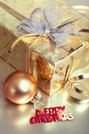 Christmas composition with gift box and bauble, closeup shot, focus on the text  photo