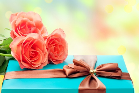Beautiful gift box and roses over bright background  photo