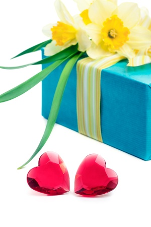 whote: Two red glass hearts with a gift box and flowers, closeup shot, isolated on whote. Valentine