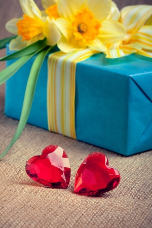 Two red glass hearts with a gift box and flowers, closeup shot, valentine photo