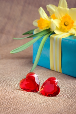 Two red glass hearts with a gift box and flowers, closeup shot, valentine's day concept photo