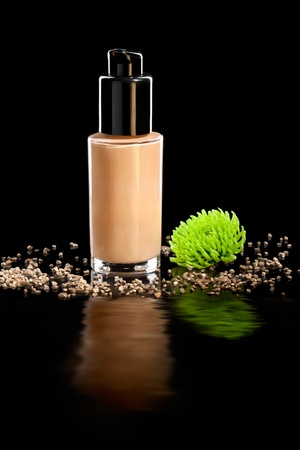 Closeup shot of foundation cream with a flower, isolated on black photo