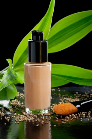 Natural cosmetics concept: foundation cream with a cosmetic brush and bamboo, isolated on black photo