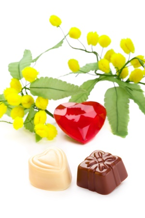 mimosa: Gift and heart shaped chocolates (dark and white chocolate) with a heart and mimosa flowers isolated on white Stock Photo