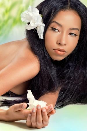 여름 해변에서 그녀의 머리에 꽃과 함께 아름 다운 젊은 여자