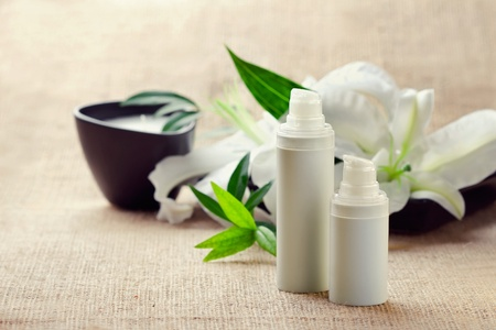 Facebody care concept: bottles of creamslotionsserums with white lily flowers, closeup shot  Stock Photo