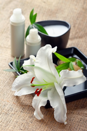 Face/body care concept: white lily flower with bottle of creams/lotions/serums, closeup shot photo
