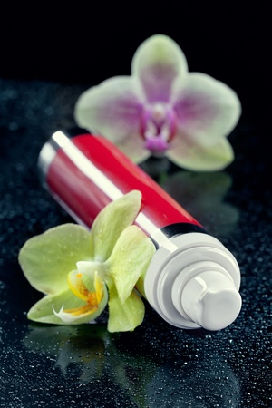 Face body care concept  bottle of cream lotion serum with orchid flowers, closeup shot, on black Stock Photo - 12838619