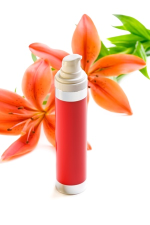Face body care concept  bottle of cream lotion with lily flowers, closeup shot, on white photo