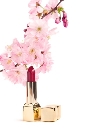 asian natural: Natural cosmetics concept  new lipstick with sakura flowers, isolated on white