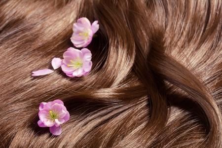 highlighted hair: Concetto di cura dei capelli: i capelli sani bella lucida con evidenziati striature dorate e fiori di sakura