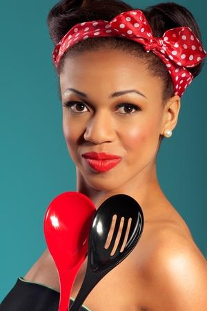 Beautiful happy joyful pinup style housewife with kitchen utensils photo