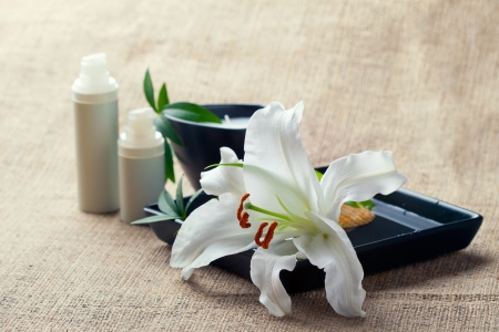 Face body care concept  bottles of creams lotions serums with white lily flowers, closeup shot