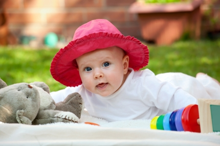Cute little baby girl playing with her toys in the garden  photo