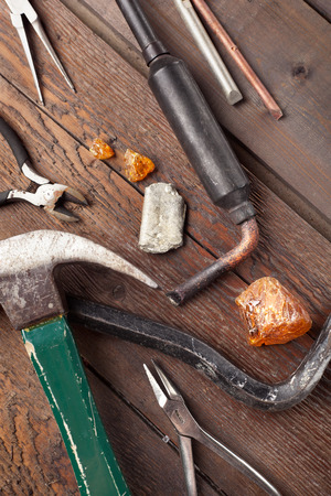 rosin: Set of old hand tools including a soldering iron with rosin and solder on wooden table