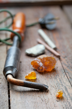 rosin: Old soldering iron with rosin and solder on wooden table, selective focus Stock Photo
