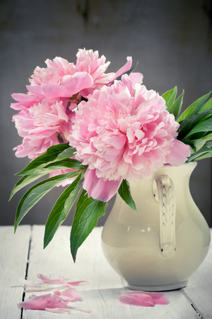 Pink peonies in retro vase on wooden table, vintage colors, toned photo photo
