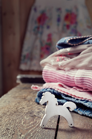 Various girls clothes on an old wooden table and a small toy wooden horse, focus on the horse photo