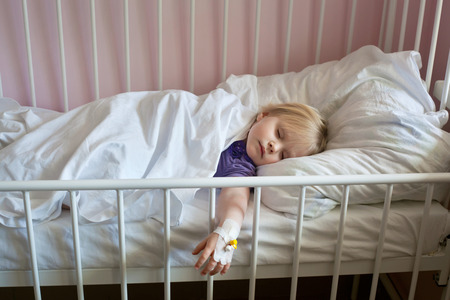 intravenous: Sick little girl with an intravenous cannula in her hand, sleeping in hospital bed