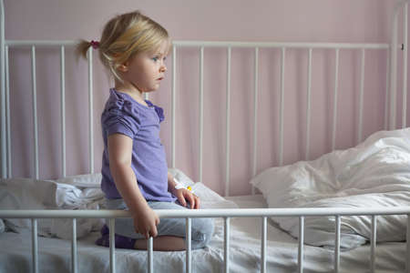 intravenous: Sick sad little girl with an intravenous cannula in her hand, sitting on hospital bed Stock Photo